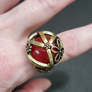 Gold tone peace sign with red ring